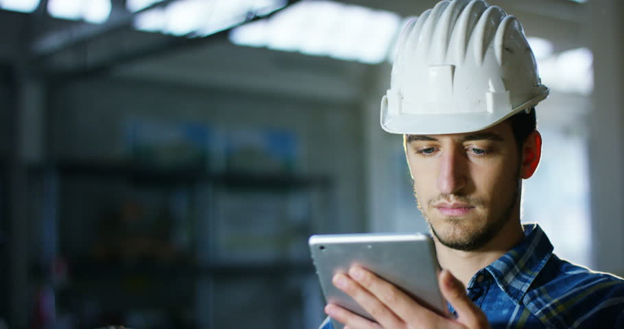 On a construction site, a worker or an engineer or architect with the tablet controls the design and construction of energy-saving. Concept: construction, worker, engineering, design. | Shutterstock HD Video #20989330