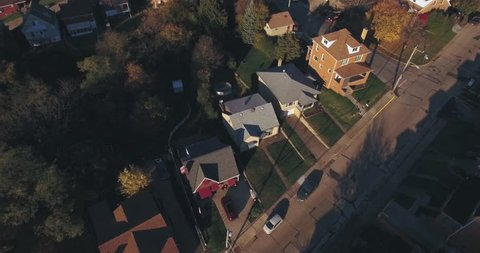An aerial view above a small Western Pennsylvania town and residential neighborhood on an Autumn evening. Pittsburgh suburb.