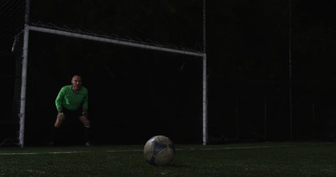 Low angle shot of a soccer player taking a penalty shot during a night game. The goalie fails to block the kick, but the ball misses the goal anyway. Slow motion.