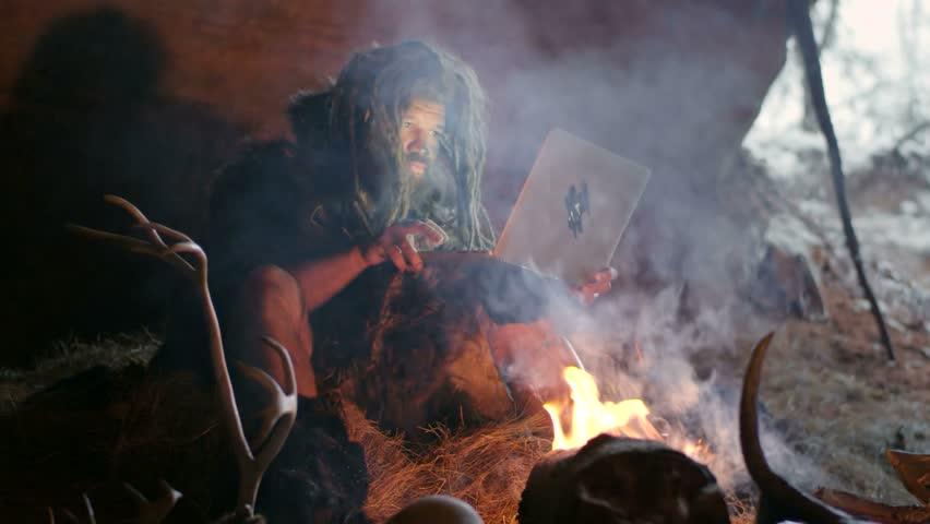 Prehistoric caveman using laptop #21021580