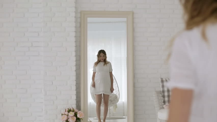 Young pregnant woman in a white dress having fun dancing in front of a mirror. Positive beautiful expectant mother moving in front of the mirror in the studio.