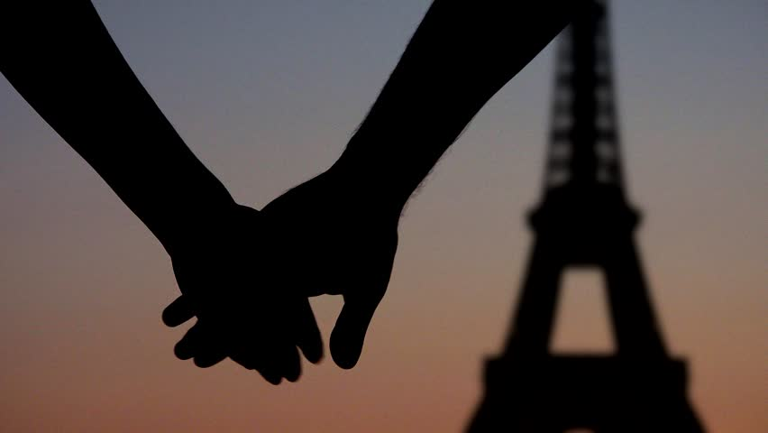 Young couple lovers joining hands in front of Eiffel tower Paris, silhouettes at sunset