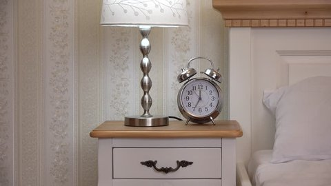 Clock and night light on bedside table, hand take the clock, vintage bedroom