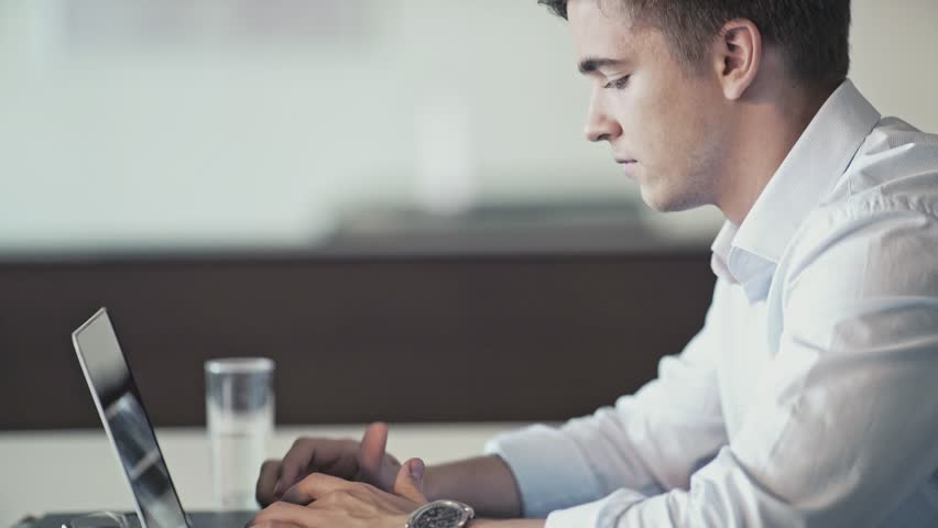 Young man with laptop in office | Shutterstock HD Video #21083980