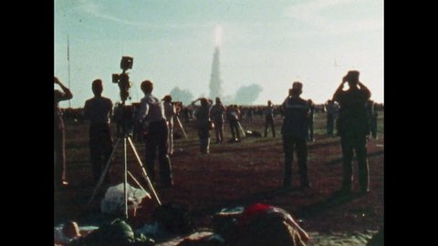 UNITED STATES: 1981: People jump and wave arms as shuttle takes off. Camera crew film shuttle lift off. People watch space shuttle in flight. Man looks through binoculars. People shield eyes from sun.