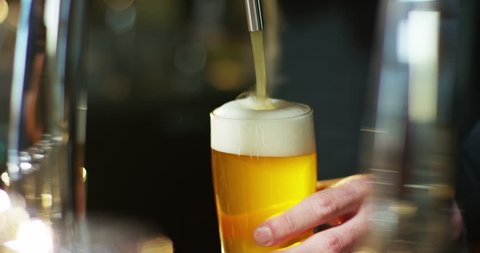 the hand of a master brewer plug a light beer foam and perfectly natural. concept of free time, freshness, time spent with friends. craft beer and traditional Irish pubs.