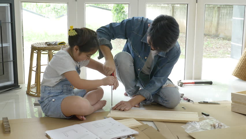 4K : Asian lovely girl helping her father assembling new DIY furniture at home together