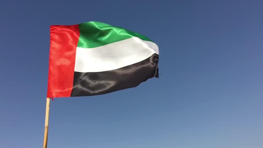 National flag of UAE hoisted high. Close up of fluttering flag of United Arab Emirates.