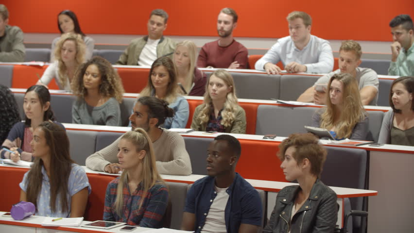 Teacher addressing students in a university lecture theatre