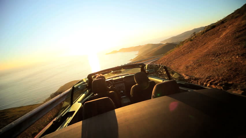 Time lapse of a driving Cabriolet on a winding coastal highway