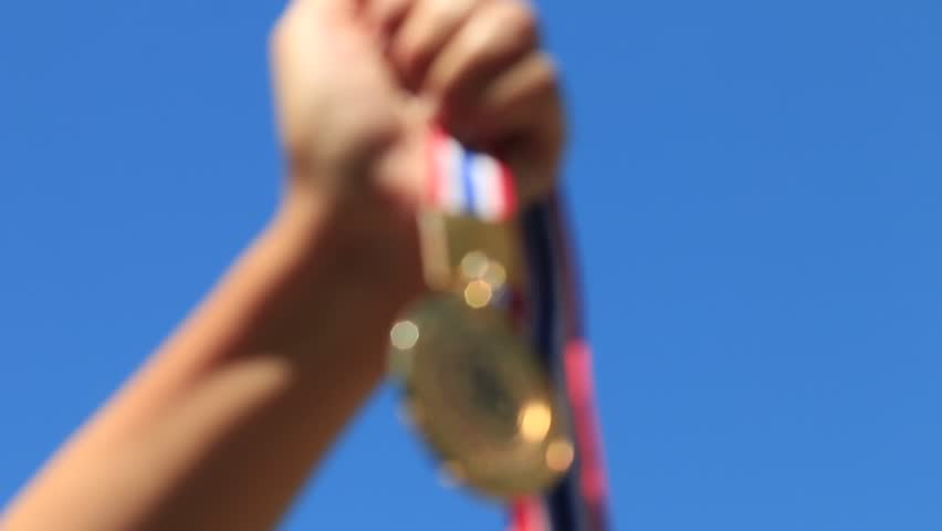 Winner and award concept : blurred of hand raised and holding gold medals against blue sky.Show competition of business in success.