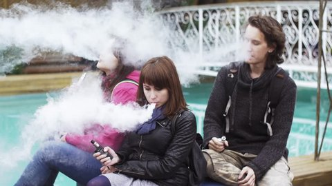 Girl and boy smoke electronic cigarette at swimming pool. Vapers. Lot of steam. Street