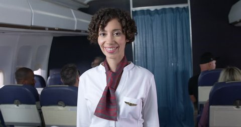 Female flight attendant stands and smiles to camera in commercial airline main cabin.  Medium shot from rear of plane with camera dolly.