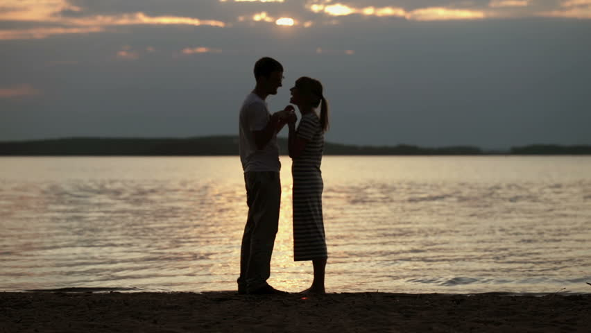Silhouettes of lovers at sunset. Young beautiful couple embracing on a shore of the lake | Shutterstock HD Video #21377200