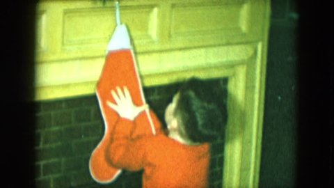 CLEVELAND, OHIO 1951: young child in pajamas touches holiday stocking and motions at camera