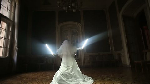 Funny joyful bride playing with lightsaber.