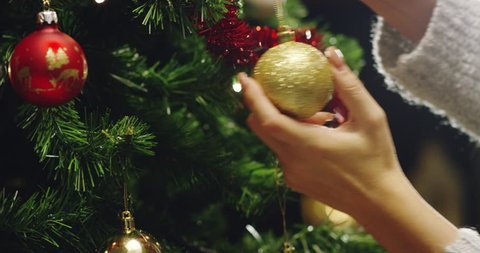 the hand of a person decorates the Christmas tree with the golden and red balls. concept of waiting for Christmas and New Year.