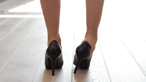 Woman trying to put too tight high heels shoes, close up.  Girl trying to put shoes on the legs but it's not suitable in size.