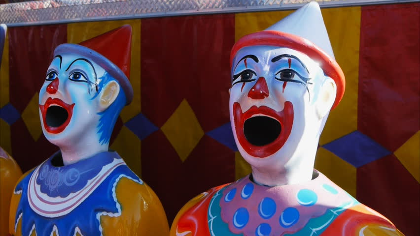 a county fair game with rotating clown heads