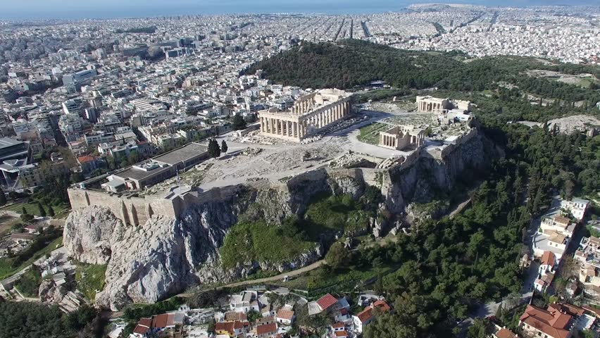 Aerial drone bird-eye view moving around front of the Acropolis of Athens ancient citadel located on rocky outcrop showing Parthenon very famous tourist attraction in Europe Greece European visit 4k