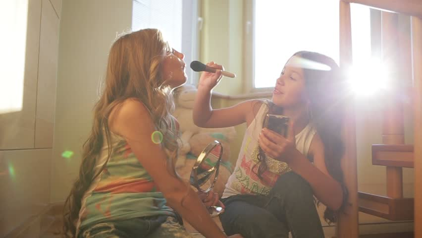 Two little girls dressing up and playing with makeup. One girl is putting the makeup to another, then both of them do so. Joyful childhood, cute smiling. Happy moments. Children games.