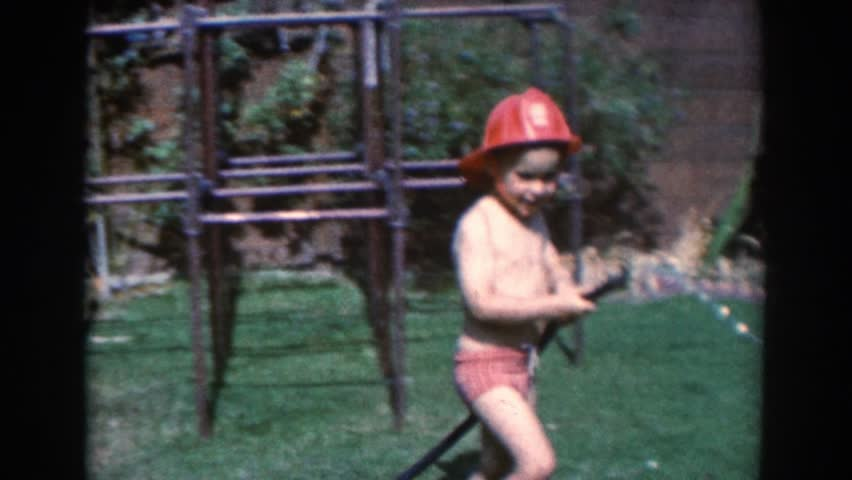 NORTH HOLLYWOOD, CALIFORNIA 1961: a small boy playing fireman in the backyard