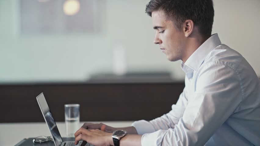 Young businessman with laptop indoors | Shutterstock HD Video #21557380