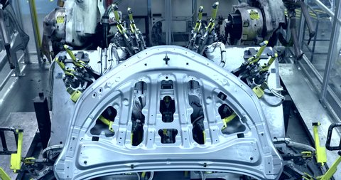 Robots are welding in production line in automobile factory