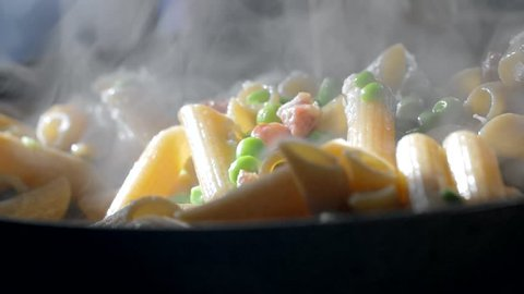 A woman is cooking penne pasta in a skillet dressed with green beans and diced bacon. Closeup slow motion shot.