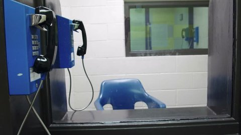 Meet area in prison jail where inmates talk on the phone with visitors behind plexiglass. Shot in 4K UHD.