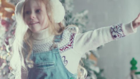 Slow motion. A cute little girl with long blond hair jumping and spinning, enjoying Christmas. Holiday in childhood. Girl like a little angel. Jumping on the bed. Children's pranks