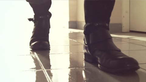 Heavy footsteps along the corridor. The old boots in slow motion. Back light and reflection in wet floor. Steps unknown male feet. Boots closeup. Shooting with dolly.