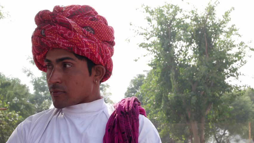 Indian man wearing a red turban talking to someone and then looks straight at the camera