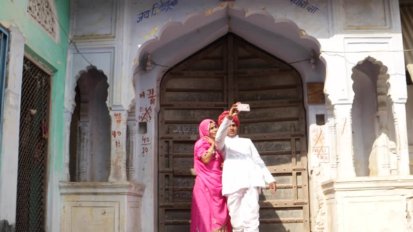 6fc782cb1c Rajasthani couple standing taking camera selfie on mobile phone photography  in front of their house with traditional architecture