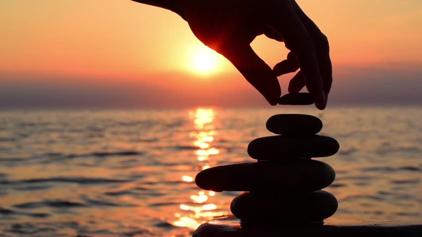 Cinemagraph loop background, balance concept. Beach scene in the cinemagraph technics: a man build zen stone pyramide at orange sea sunset background. Sea surf, wave, sun road. Cinemagraph HD footage.