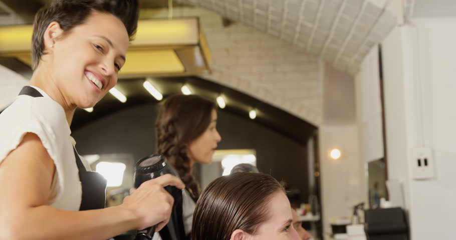 Female hairdresser blow drying her client hair at the hair salon
