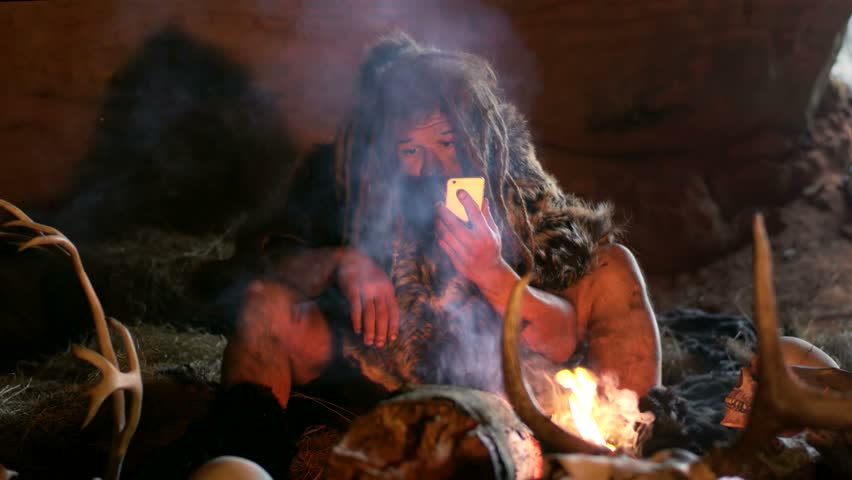 Prehistoric caveman using smartphone