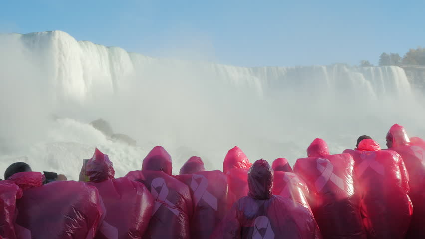 Group of tourists in red raincoats floats on the boat at Niagara Falls. Admiring the waterfall near. Back view
