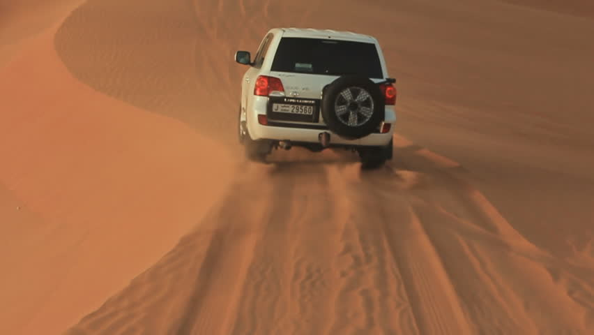 ABU DHABI, UAE - AUGUST 20, 2014: Desert Safari SUVs bashing through the arabian sand dunes. View from the car 13.