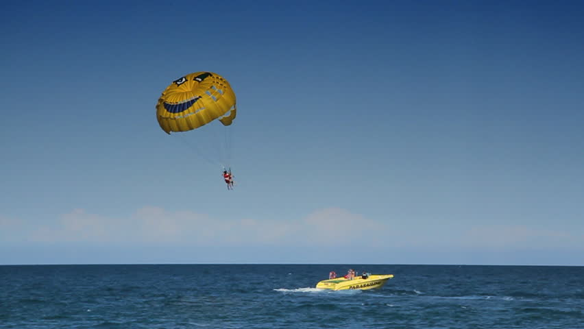 Person flying on a parachute is pulled on a rope by a boat.