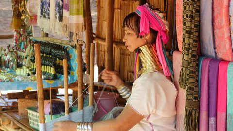 Karen Long Neck woman weaving and smiling at hill tribe village in Chiang Rai, northern Thailand.
