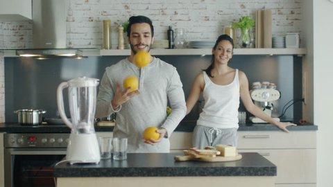 On the Kitchen Beautiful Couple Makes Breakfasts. Guy Impresses His Lady By Juggling with Oranges. Shot on RED Cinema Camera in 4K (UHD).