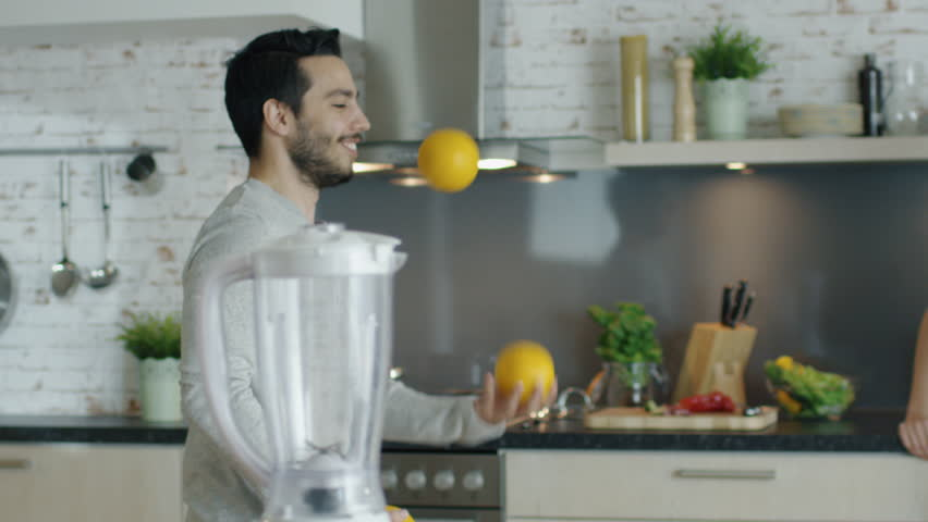 Lively Young Man Impresses His Girlfriend by Juggling Oranges on the Kitchen. Shot on RED Cinema Camera in 4K (UHD).