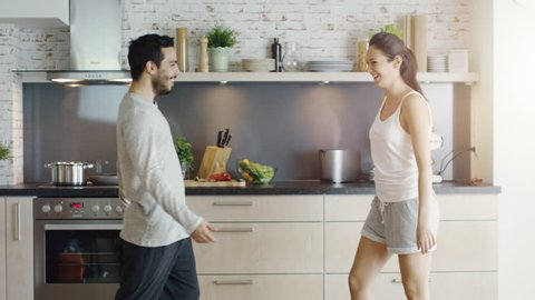 Happy Couple on the Kitchen. Girl Jumps into Guy's Arms. Shot on RED Cinema Camera in 4K (UHD).