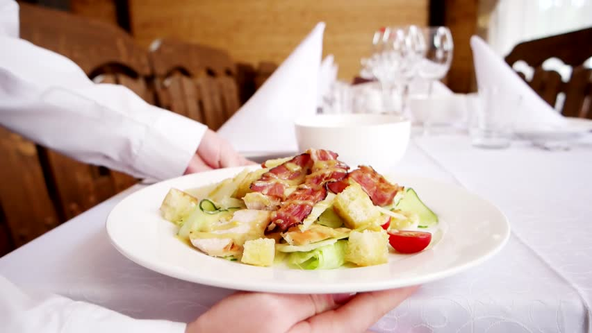 Waiter brings dish with salad in restaurant puts plate on covered with white tablecloth, cutlery and dishes are on table in cafe Caesar salad is served on table | Shutterstock HD Video #21758320