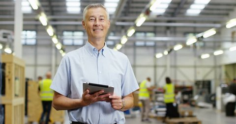 4k, Portrait of a mature manger using digital tablet in a warehouse. Slow motion.