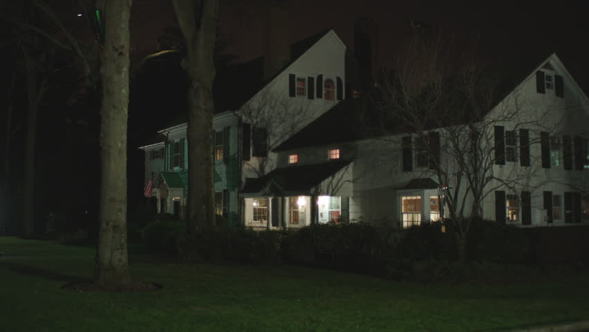 night Holds then pans right along upscale large rambling nice two story house eastern wood house country estate Bed Breakfa street Country Inn, some lights on, mostly bare trees, large property, late