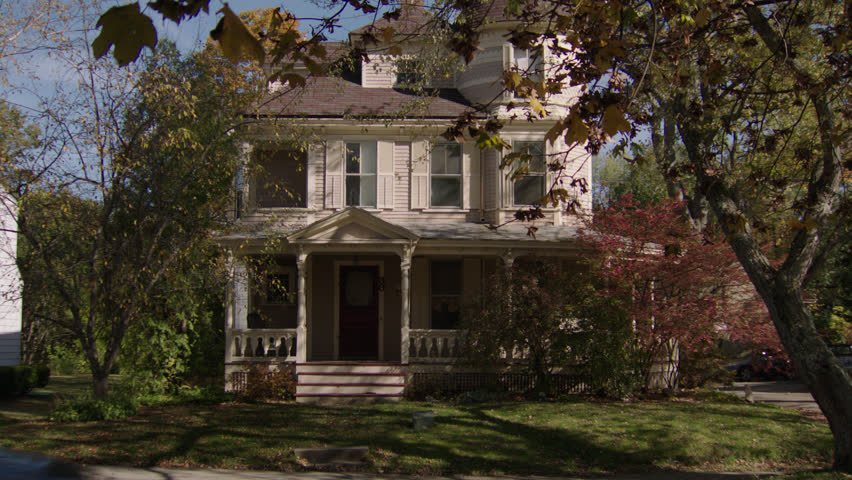 Day tilt tree front beige wood clapboard house , wrap around porch, turret, bay windows, screened red door, autumn, fall trees, breezy, car (Oct 2012)