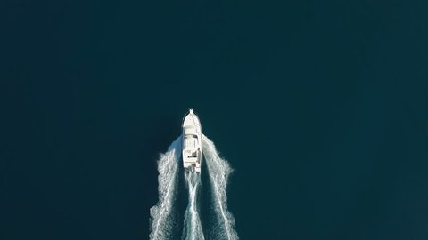 Aerial - Top down tracking shot of a bigger speed boat cruising on water