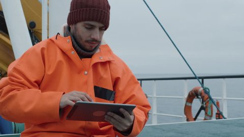 Casualy Dressed Fisherman Using Tablet Computer with Navigation Maps while Traveling on Ship. Shot on RED Cinema Camera in 4K (UHD).